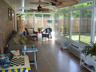 Interior view of sunroom with tile flooring, ceiling fans, and furniture..